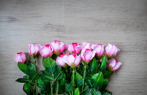 Rosa rosen auf lokalisiertem hölzernem hintergrund.