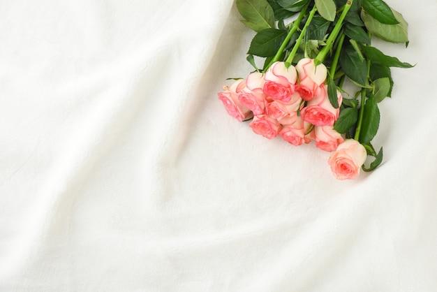 Rosa rosen auf weißem pelz flatlay