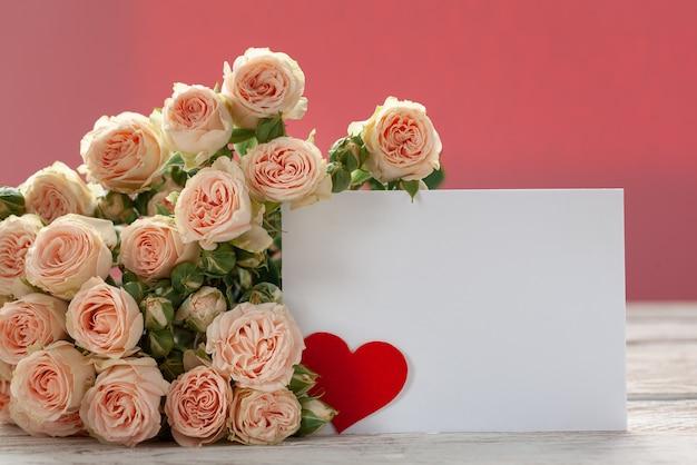 Rosa rosen blüht mit geschenkkarte und rotem papierherzen auf rosa