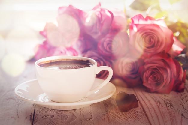 Rosa rosen des tasse kaffees und des blumenstraußes auf tabelle