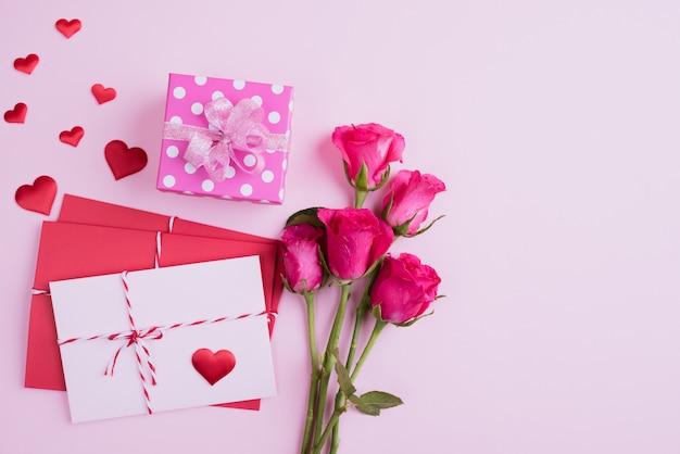 Rosa rosen, geschenkbox mit rotem herzen und rote rosa buchstabenabdeckung auf rosa hintergrund