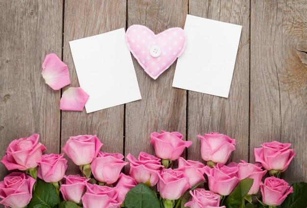 Rosa rosen, handgemachtes spielzeugherz und leere valentinstaggrußkarten oder fotorahmen