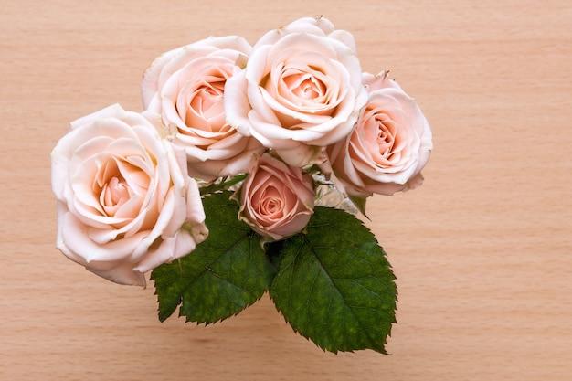 Rosa rosen in einer vase auf einem hölzernen schreibtisch.