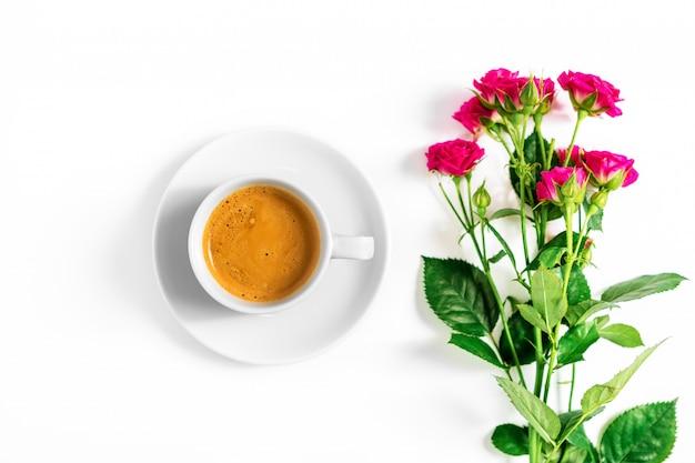 Rosa rosen mit einem tasse kaffee lokalisiert auf einem weißen hintergrund