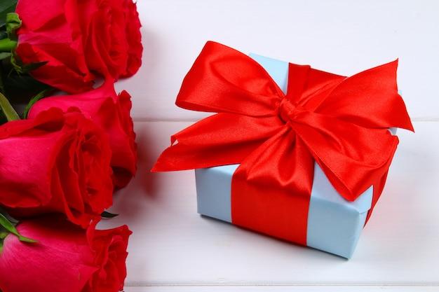 Rosa rosen mit einer geschenkbox mit einem bogen gebunden. vorlage für den 8. märz, muttertag, valentinstag.