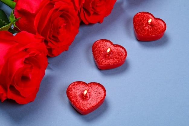 Rosa rosen mit roten kerzen eines herzens. vorlage für den 8. märz, muttertag