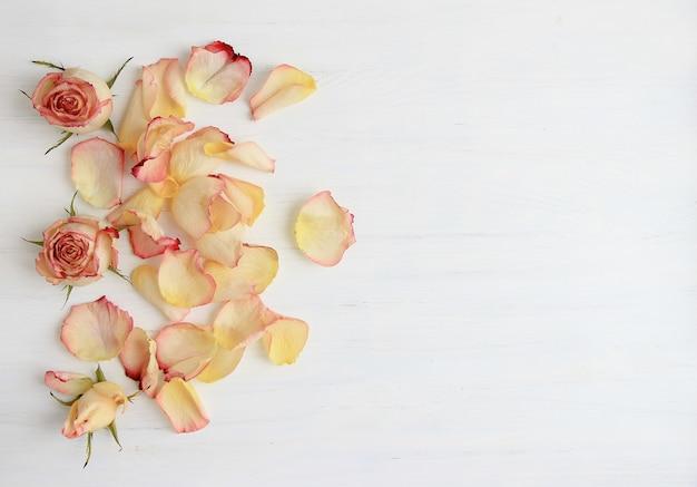 Rosa rosen, rosafarbene blumenblätter auf hölzernem hintergrund