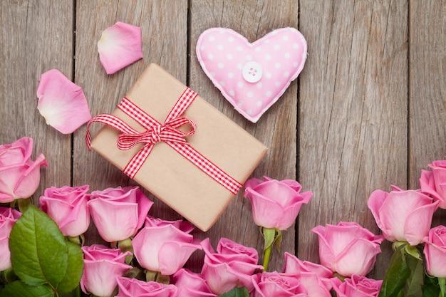 Rosa rosen über holztisch mit valentinstag-geschenkbox und herzspielzeug