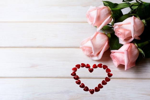 Rosa rosen und herz von roten blumenblättern