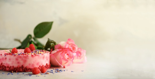 Rosa rosen und himbeerkuchen mit frischen beeren, rosmarin, trockene blumen auf konkretem hintergrund.