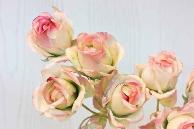 Rosa rosen und knospen auf einem weißen hintergrund. künstliche blumen im innenraum