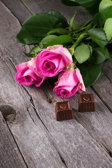 Rosa rosen und schokoladen in form von herzen auf einem dunklen hintergrund