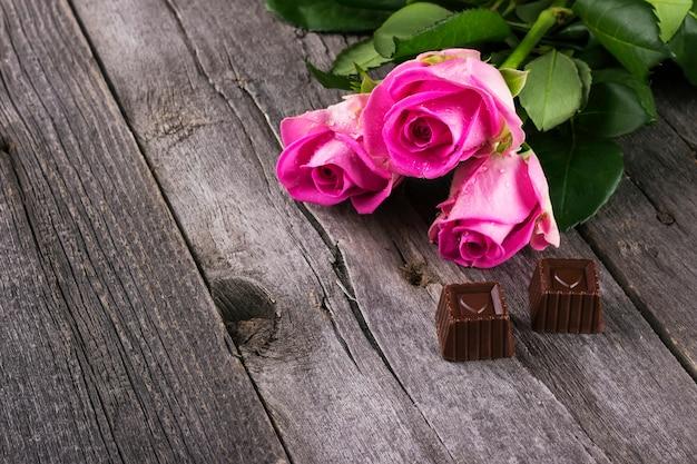 Rosa rosen und schokoladen in form von herzen vor einem dunklen hintergrund