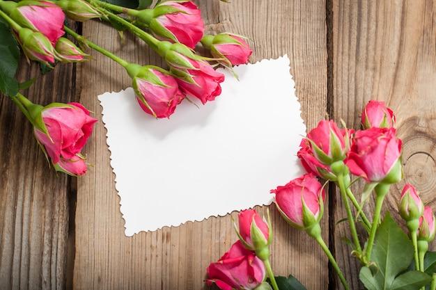 Rosa rosen und weiße karte mit einem platz für einen text auf einem holztisch
