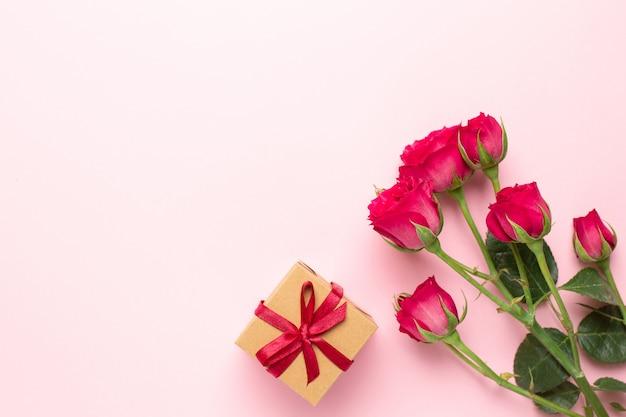 Rosa rosenblumen und anwesendes geschenk auf rosa