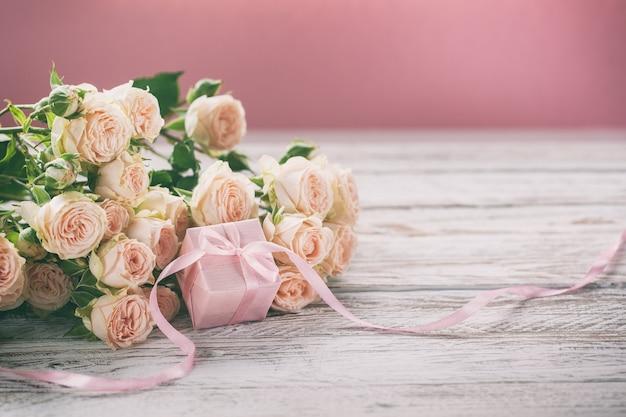 Rosa rosenblumen und geschenk oder präsentkartonrosahintergrund.