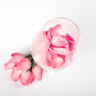 Rosa rosenblumenblätter im glas auf tabelle