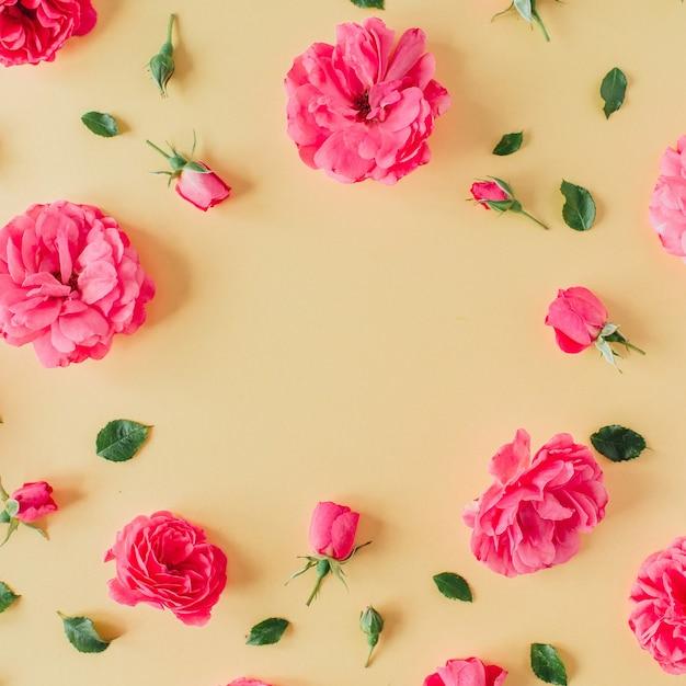 Rosa rosenblumenmuster auf gelber oberfläche mit leerem modellkopieraumrahmen