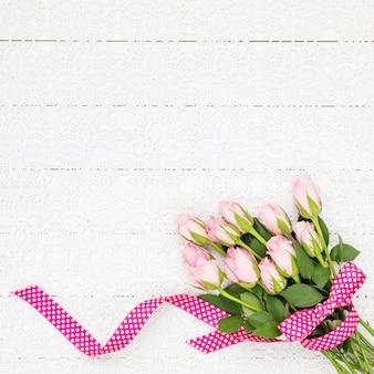 Rosa rosenblumenstrauß auf weißer tischdecke