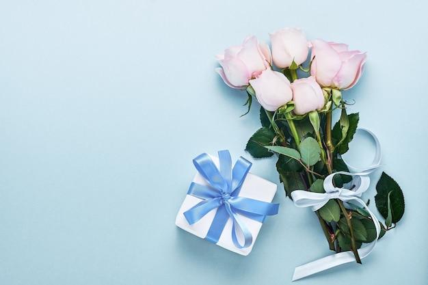Rosa rosenblumenstrauß mit band und geschenkbox über schönem blauem hintergrund. grußkartenvorlage mit kopierraum