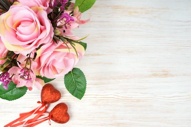 Rosa rosenstrauß und valentinstagherzen auf weißem hölzernem hintergrund. draufsicht, flach mit kopierraum liegen
