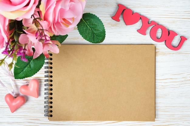 Rosa rosenstrauß und valentinstagherzen mit papierblock und wörtern, die ich sie auf weißem hölzernem hintergrund liebe. draufsicht, flach mit kopierraum liegen