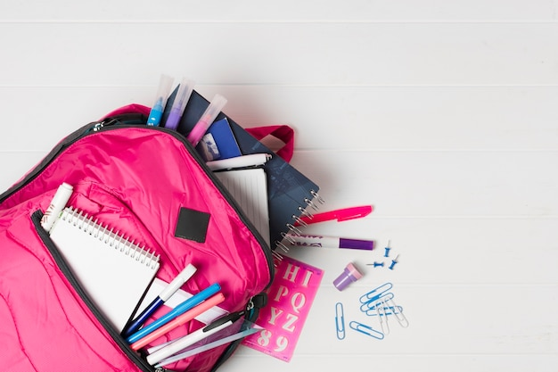 Rosa rucksack mit draufsicht des schulbedarfs