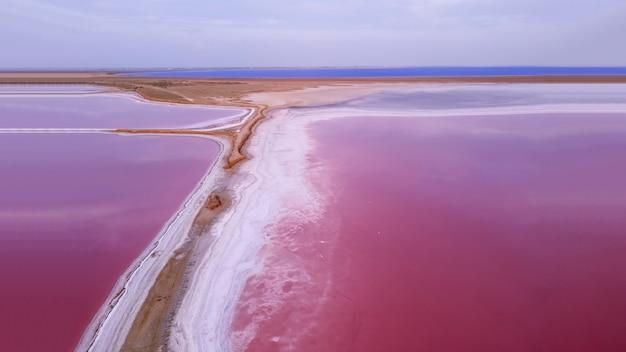 Rosa salzsee. das malerische ufer der lagune ist mit einer dicken salzschicht bedeckt, die sich beim verdampfen des wassers bildet.