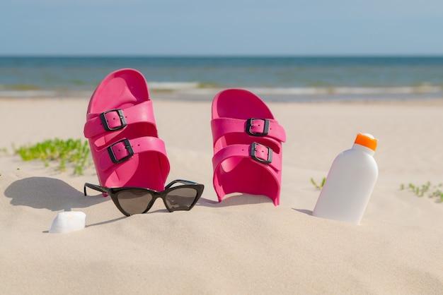 Rosa sandalen, sonnenbrille und sonnencreme am strand an einem schönen sonnigen tag.