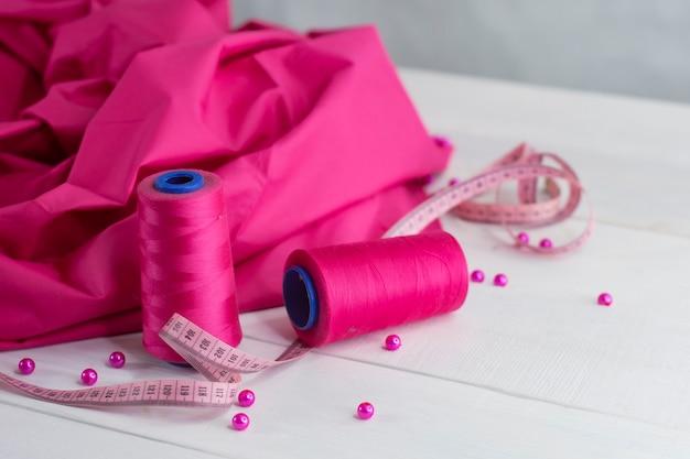 Rosa satinstoff mit faden und zentimeter auf holzhintergrund mit perlen.