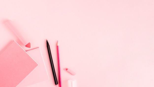 Rosa satz bürowerkzeuge auf farbiger oberfläche