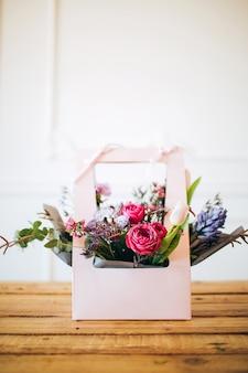Rosa schachtel mit blumen. schachtel mit pfingstrosenrosen und weißen tulpen. gartenblumen in blumentöpfen. wildblumen.