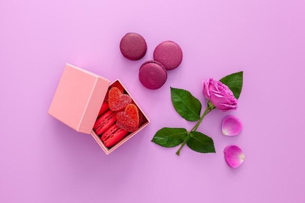 Rosa schachtel mit marmelade und makronen und einer schönen rose