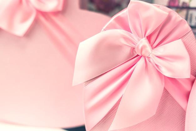 Rosa schachteln für geschenke in form von herzen. romantische urlaubsverpackung. nahaufnahme, kopierraum