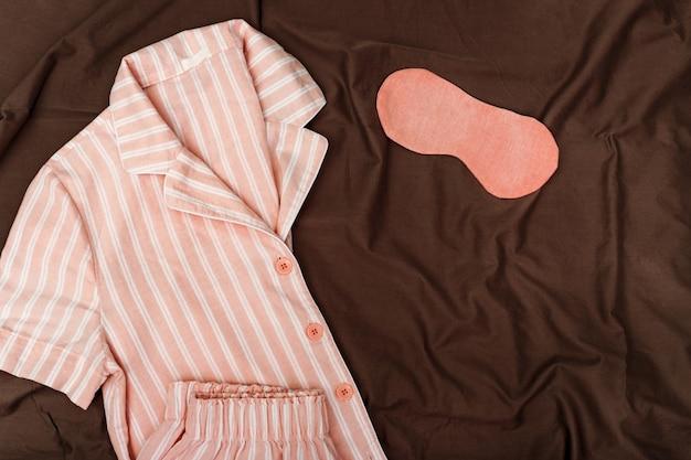 Rosa schlafanzug für mädchen, schlafbrille auf dunklem baumwolltuch