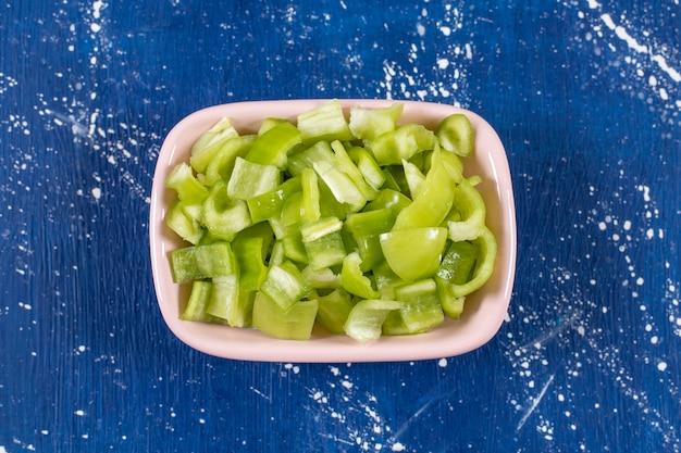 Rosa schüssel mit frischem grünem paprika auf marmoroberfläche.