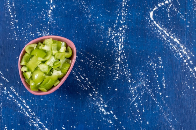 Rosa schüssel mit in scheiben geschnittenen grünen paprika auf marmoroberfläche