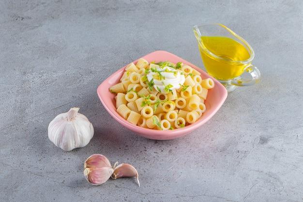 Rosa schüssel mit köstlichen gekochten nudeln mit olivenöl auf steinoberfläche.