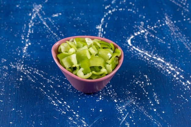 Rosa schüssel mit reifen grünen paprikaschoten auf marmortisch.