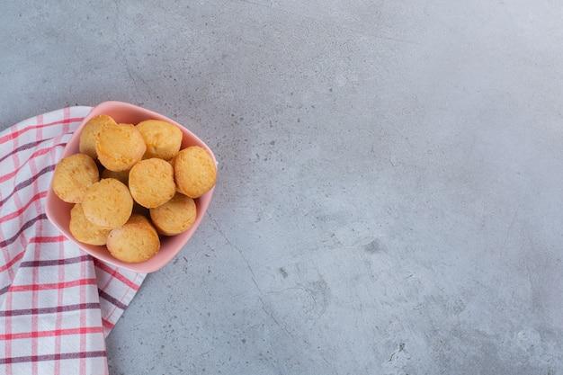 Rosa schüssel mit süßen minikuchen auf stein.