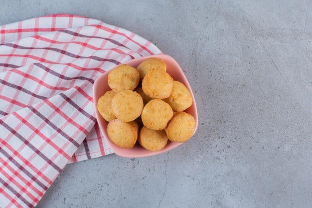 Rosa schüssel mit süßen minikuchen auf steinhintergrund.