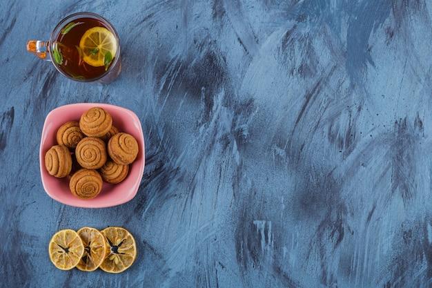 Rosa schüssel von mini-zimtkuchen mit glas tee auf steinhintergrund.