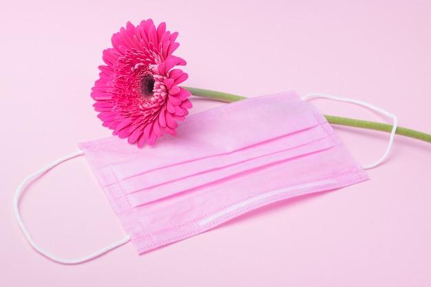 Rosa schützende medizinische gesichtsmaske und gerbrablume auf einem rosa hintergrund