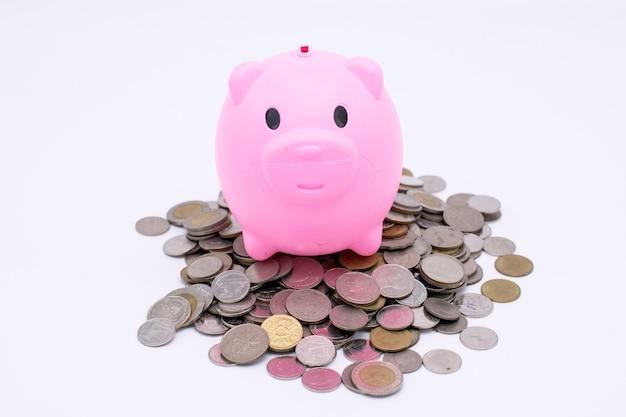 Rosa schwein, das auf geldmünze auf weißem hintergrund, abwehrgeldkonzept spart
