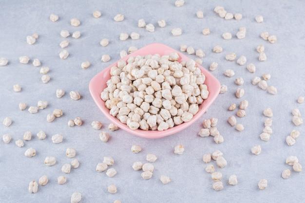 Rosa servierschüssel, überfüllt mit einem haufen kichererbsen, auf marmoroberfläche