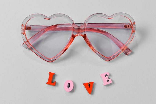 Rosa sonnenbrille auf einem blauen hintergrund mit liebestext. draufsicht.
