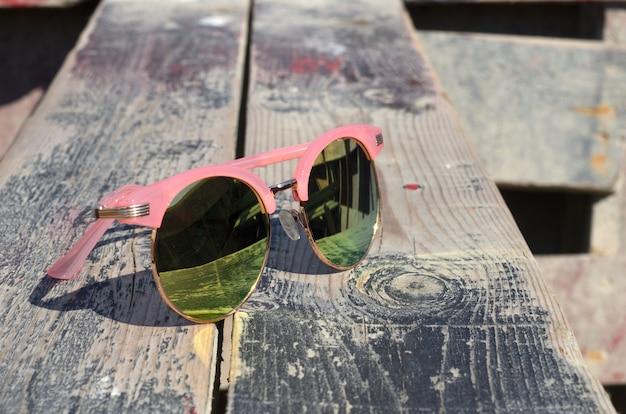 Rosa sonnenbrille gegen die sonne auf einem hölzernen nahe dem meer