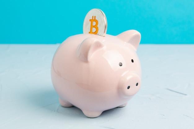Rosa sparschwein auf blauem raum mit bitcoin-münze