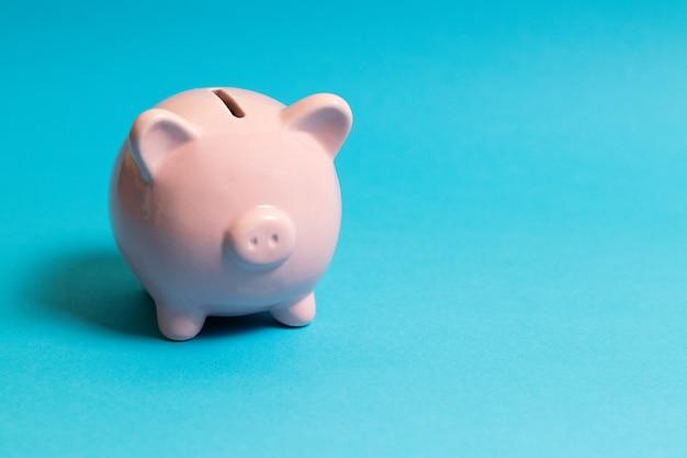 Rosa sparschwein auf einem blauen papier
