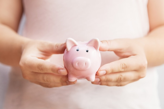 Rosa sparschwein in den händen der frau. mädchen im rosafarbenen holding-sparschwein